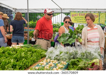 WASHINGTON DC - MAY 24, 2015: Shoppers at a farmers market choose from a variety of fresh vegetables for sale. Located in the Dupont Circle neighborhood. - stock photo