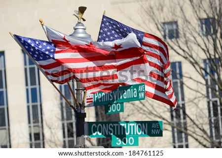 Washington DC, Pennsylvania Avenue and Constitution Avenue junction street signs with DC and United States of America flags on the same post  - stock photo