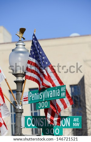 Washington DC, Pennsylvania Avenue and Constitution Avenue junction street signs with United States of America flag on same post - stock photo