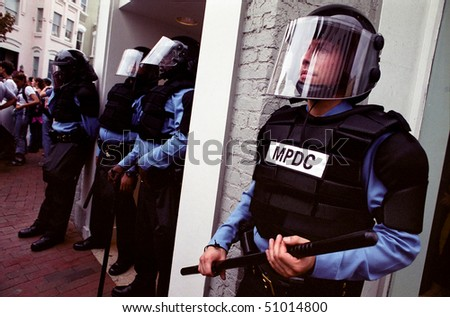 WASHINGTON, DC - SEPT 27: Police in full riot gear and batons guard Gap stores during anti-sweatshop protests in Washington, DC on Sept. 27, 2002. - stock photo