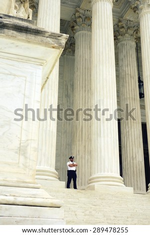 WASHINGTON DC, U.S.A. - APRIL  14, 2015: A security guard outside the Supreme Court building in Washington DC.