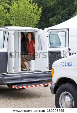 Washington, DC USA - August 25, 2011:  Female climate protesters arrested for civil disobedience and put in police van for protesting against Keystone XL Pipeline in front of the White House.