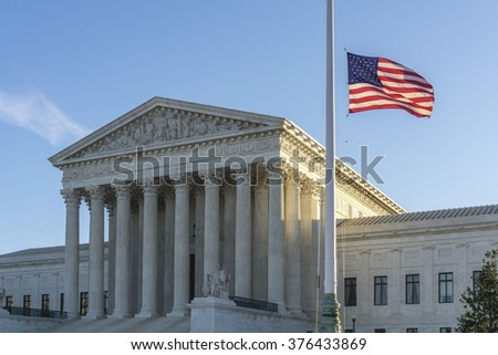 WASHINGTON, DC, USA - FEBRUARY 14, 2016: Flags fly at half-staff at the United States Supreme Court as the sun rises on the first day after Justice Antonin Scalia's death was announced.   - stock photo