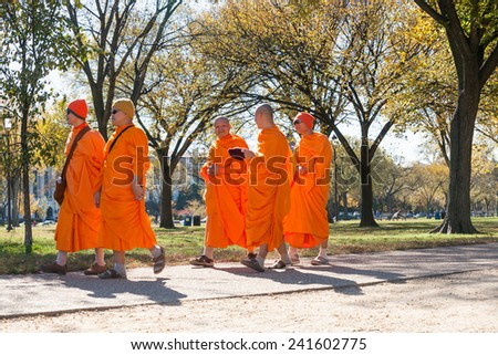 WASHINGTON DC, USA - OCTOBER 28;Five Buddhist Monks walk in Washington DC park, dressed in the bright saffron robes they move along the path talking on October 28, 2014 in Washington DC, USA. - stock photo