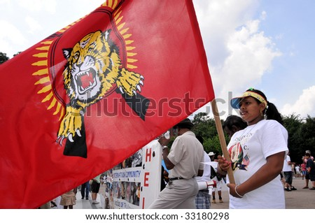 WASHINGTON - JULY 4: A woman holds the Tamil Tigers flag in a rally in front of the White House in Washington on July 4, 2009. The rally blamed Sri Lanka for human rights violations against Tamils. - stock photo