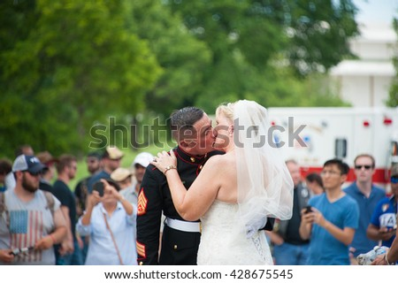WASHINGTON  ?? MAY 29: Staff Sgt. Tim Chambers, known as the saluting marine, kisses his new bride at Rolling Thunder, an annual motorcycle rally, on May 29, 2016 in Washington, DC.   - stock photo