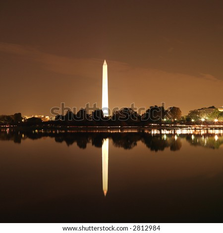 Washington Monument reflected in water at night in Washington, D.C., USA.