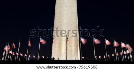 Washington Monument with waving United States flags at night - stock photo