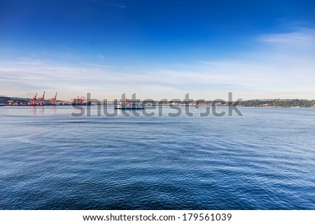 Washington State Ferry crosses Elliot Bay on a route from Seattle to Bainbridge Island. Port of Seattle in the background - stock photo
