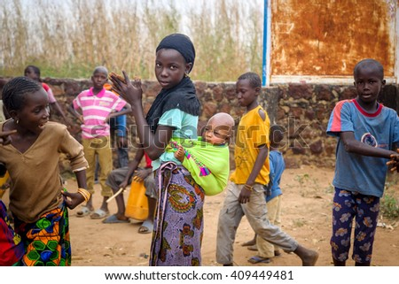 WASSU/GAMBIA - NOVEMBER 18, 2013:Very young african mother with her newborn child hanging on her back stands with the group of children on the street of Wassu, Gambia.