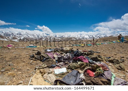 Waste and old clothes with the Himalayas mountain range in the background. Friendship Highway bewteen Nepal and Tibet. China 2013. - stock photo