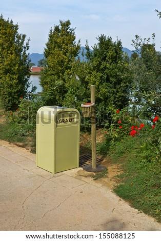 waste bin in a flower garden - stock photo