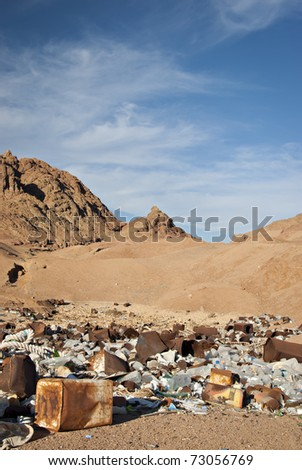 Waste dump in the desert, rusted cans in the foreground, mountains in the background against a blue sky. South Sinai, Egypt.