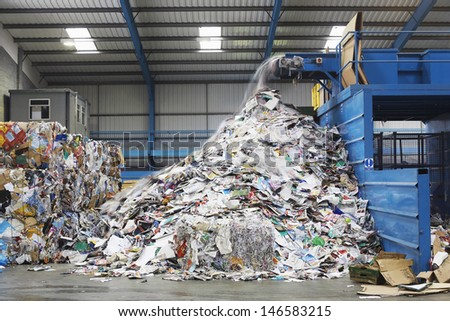 Waste falling on pile from conveyor belt at recycling factory - stock photo