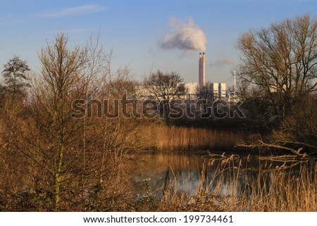 Waste incineration plant letting off steam on an autumn day with wetlands in the foreground - stock photo
