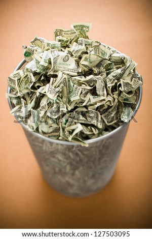 Waste paper basket with crumpled money - stock photo