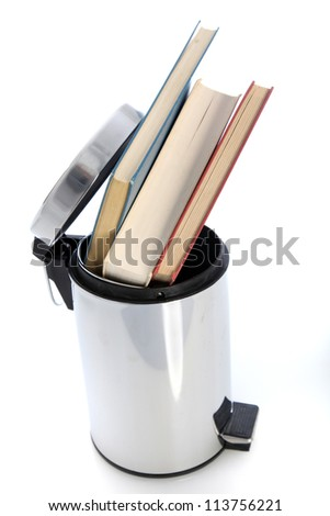 Waste paper bin filled with books Cylindrical metal waste paper bin filled with hardcover books possibly from a student venting his or her frustration with the education system - stock photo