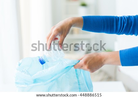 waste recycling, reuse, garbage disposal, environment and ecology concept - close up of hand putting empty used crashed plastic water bottles into rubbish bag at home - stock photo