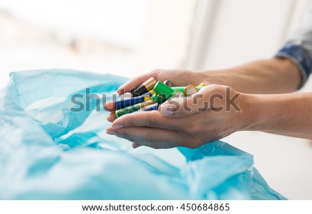 waste recycling, reuse, garbage disposal, environment and ecology concept - close up of hands putting alkaline batteries to rubbish bag - stock photo