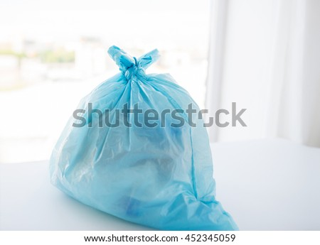 waste recycling, reuse, garbage disposal, environment and ecology concept - close up of rubbish bag with trash or garbage at home - stock photo