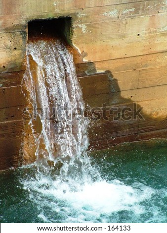 Waste water puring out into discolored water - stock photo