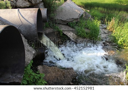 Waste water runs from the pipe  - stock photo