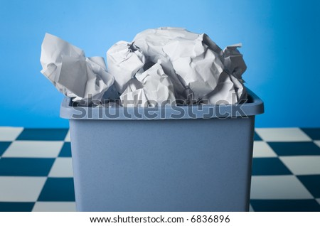 Wastebasket full up with crumpled paper. Front view - stock photo