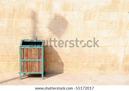 wastebasket in front of wall - stock photo