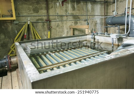 Wastewater aeration basin bubbling in a building - stock photo