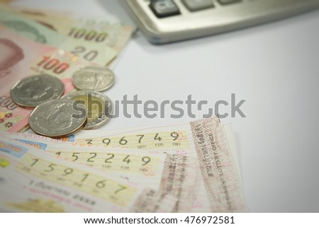 Wasting money on gambling and betting concept. Thai lottery and Thai currency on white background. Thai money isolated on white background.