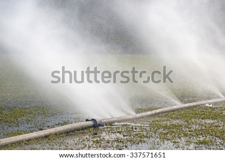 wasting water - water leaking from hole in a hose - stock photo