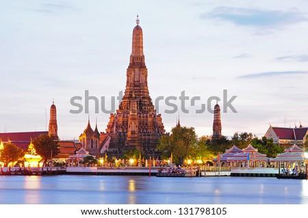 Wat Arun across Chao Phraya River during sunset in Bangkok, Thailand - stock photo