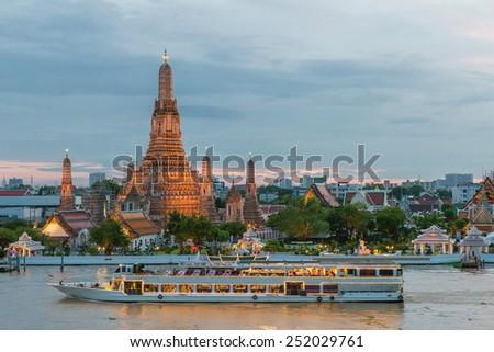 Wat Arun and cruise ship in night ,Bangkok city ,Thailand - stock photo