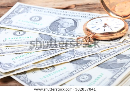 watch and dollar bills on wooden table background