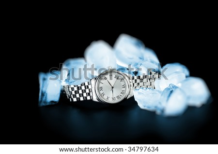 Watch and ice isolated on black - stock photo