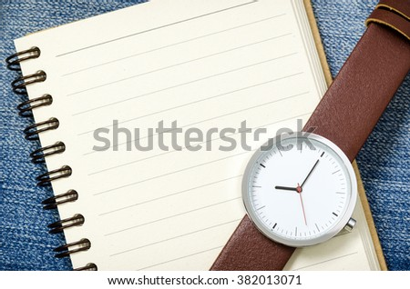 watch and notebook with blank pages on blue jeans