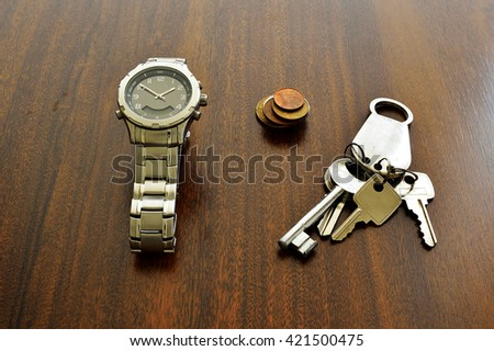 Watch, Coins and Keys over a wood table - stock photo
