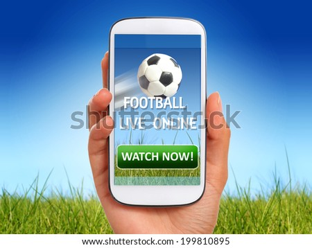 Watch football on a mobile device. - stock photo