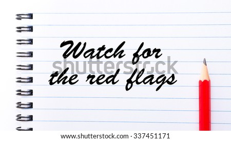 Watch for the red flags written on notebook page, red pencil on the right. Motivational Concept image