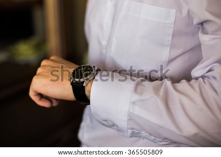 watch on a man's hand, the fees of the groom, wedding preparation, preparation for work, putting the clock on the hand, fasten clock watch time, man's style, sense of style  - stock photo