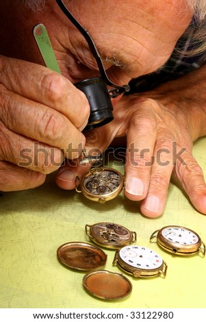 watch repair craftsman repairing old watch with tweezer - stock photo