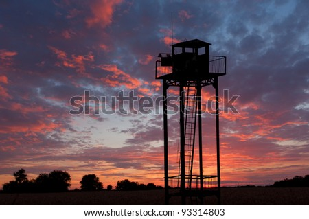 watch tower on sunset sky background - stock photo