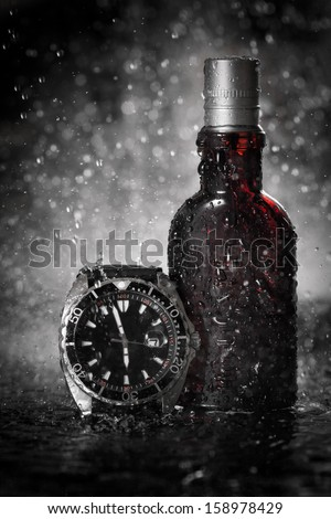 Watches and perfume under water drops - stock photo
