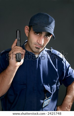 Watchful security officer in uniform, holding a gun
