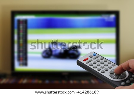 Watching a motorbike race in the television, with a tv remote control in the hand