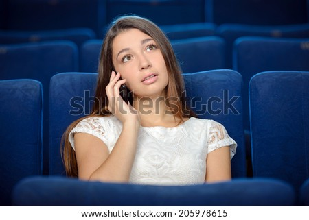 Watching a movie. Young woman talking on the phone while watching a movie at the cinema - stock photo