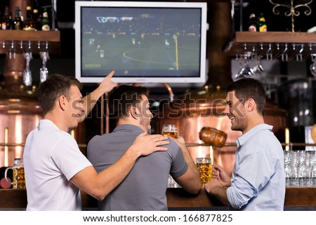 Watching a soccer match. Rear view of three happy men watching a soccer match and gesturing while sitting in bar - stock photo