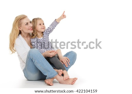 Watching above. Portrait of a gorgeous adult woman sitting with her little beautiful daughter pointing away copyspace on the side on white background. - stock photo