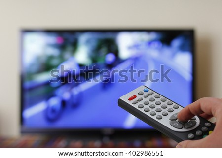 Watching cycling in the television, with a tv remote control in the hand