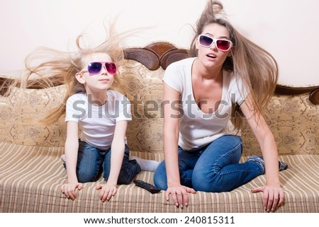 watching 3D movie surprised young beautiful woman with blond little girl sitting in 3D glasses experiencing real life special effects hair blown portrait - stock photo